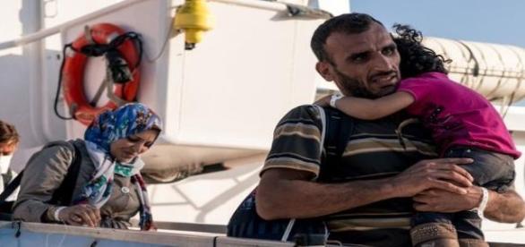 Un padre lleva en brazos a su hija al desembarcar en Italia. MSF