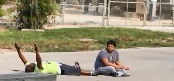 Momentul în care bărbatul de culoare deși este întins pe jos și are mâinile ridicate în aer, este împușcat