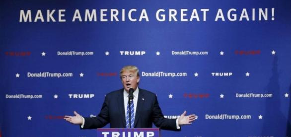 Republican candidate Donald Trump stands infront of a campaign poster. Via theodysseyonline.com