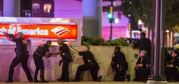 Policías tratando de inmovilizar a los francotiradores frente a la sede de Bank of America en Dallas