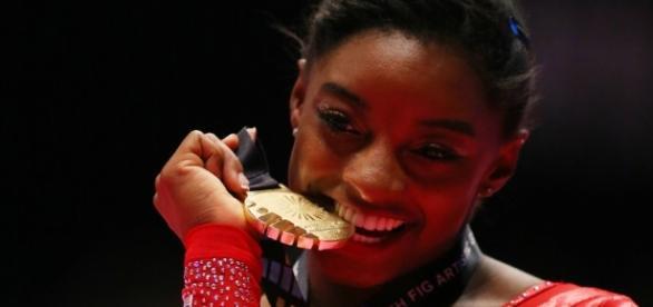 Simone Biles triunfadora mordiendo el oro en Rio 2016