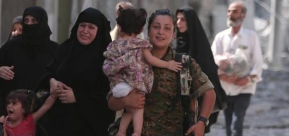 Combatente das Forças Democráticas Sírias ajudam famílias na libertação de Manbij, cidade que estava sob o controle do Estado Islâmico