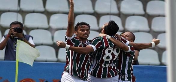 Abraçado por Scarpa (esquerda) e Marcos Júnior (direita), Henrique Dourado celebra gol da vitória sobre o América-MG (Foto: Net Flu)