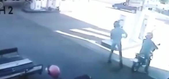 Dois bandidos chegam no posto em uma motocicleta.