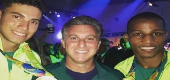 Luciano Huck ao lado de Thiago Braz e Robson Conceição