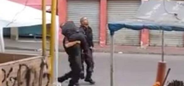 O agente baleado é carregado por um outro policial