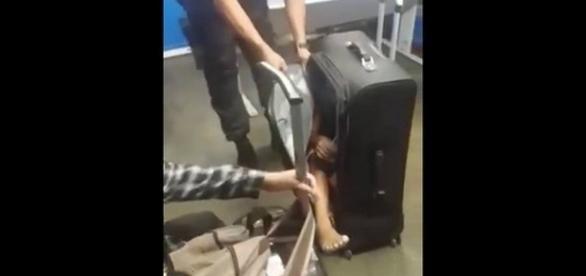 Momento em que o policial tirou a criança da mala. Imagem/ Fonte internet