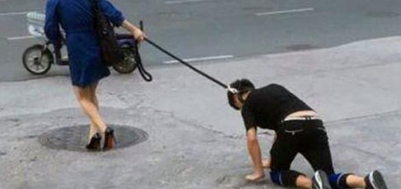 Mulher andou nas ruas com homem peso na coleira.