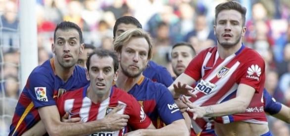 Jugadores del Barcelona y del Atlético luchan por rematar