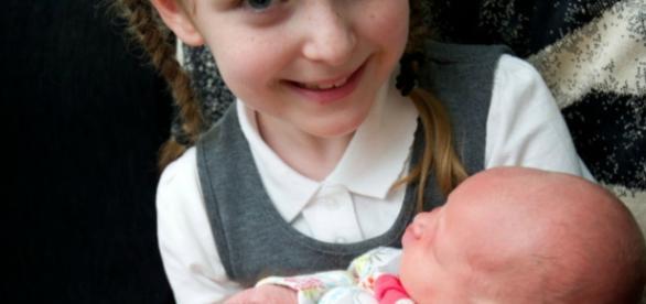 Libby, de sete anos, segurando a bebê