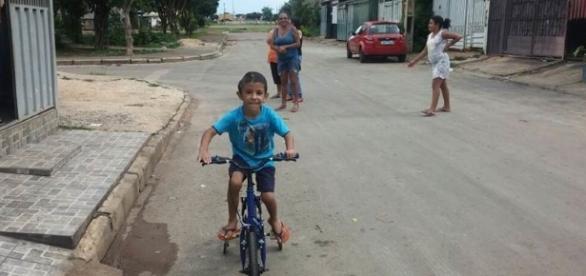 Criança anda feliz em sua bicicleta presenteada por policiais.