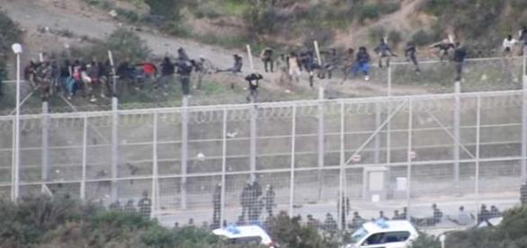 Imigranți africani încearcă să forțeze frontiera dintre Maroc și enclava spaniolă Ceuta, pentru a ajunge în UE - Foto: captură YouTube