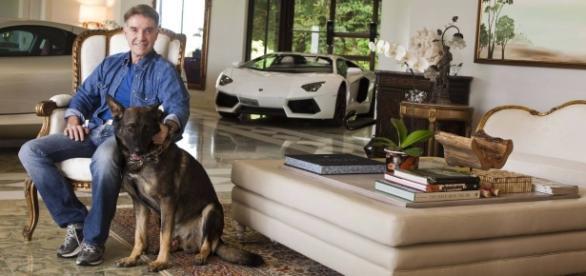 O empresário Eike Batista em sua casa ao fundo de sua Lamborghini