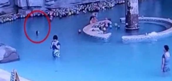Apesar da piscina estar lotada, ninguém viu afogamento. Na segunda foto, veja imagem da criança, sem vida (Shanghai Daily)