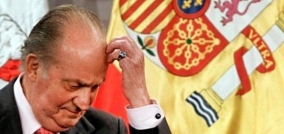 El rey emérito Juan Carlos I junto a la bandera