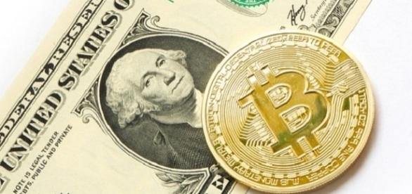 Bitcoin coin and a US dollar [Image Credits:Tombark/Pixabay]