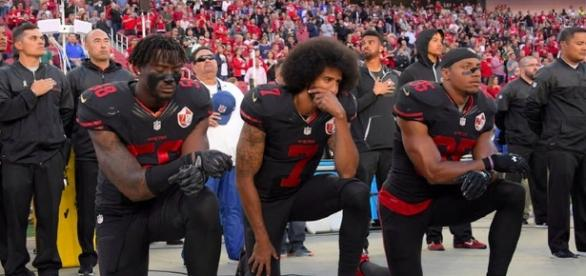 San Francisco 49ers' Eli Harold, Colin Kaepernick and Eric Reid kneel during the national anthem. [Image via Marie Louise Meewah/Flickr]