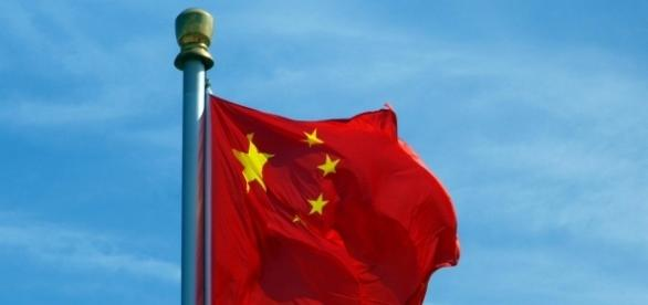 Chinese flag waving in Tian An Men Square, Beijing, on a sunny day. Image Elisa Tirabassi