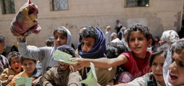 Yemenis present documents in order to receive food rations provided by a local charity, in Yemen's capital, Sanaa.