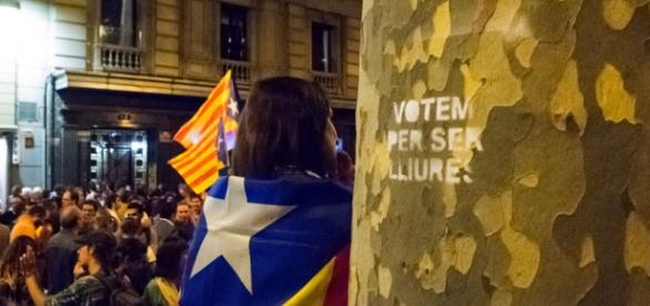 """Women dressed in the Catalan independence flag stands next to a spray painted tree that reads in Catalan """"We vote for being free"""""""