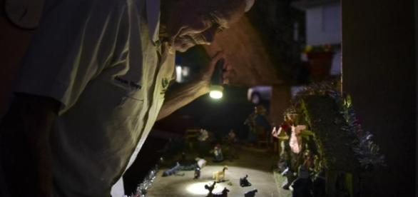 A man shines a torch over a nativity scene in Puerto Rico. Photo Credit: The Chicago. Tribune