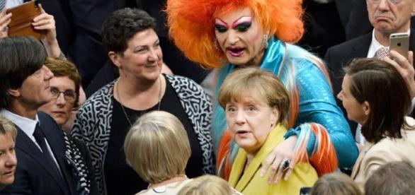 Olivia Jones abbraccia la Merkel subito dopo l'elezione del nuovo Presidente davanti allo sguardo divertito di Loew