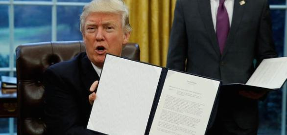 Donald Trump signs the order Photo credit to Vanhuy Nguyen