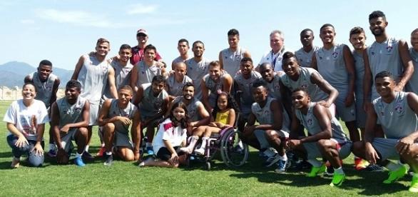 Na cadeira de rodas, menina Rhyana recebeu carinho de elenco do Fluminense (Foto: Thyago Bokel/Divulgação FFC)