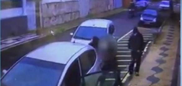 Na imagem é possível ver o momento em que os dois homens encapuzados abordam a mulher para assaltá-la.