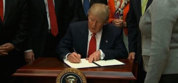 Donald Trump is signing the order. Photo via CNN.com