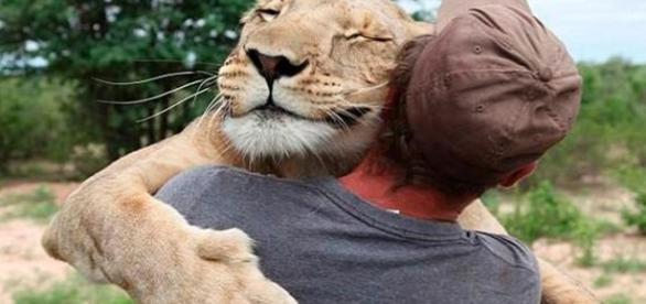 Valentin Gruener abraçando leoa que foi abandonada quando filhote