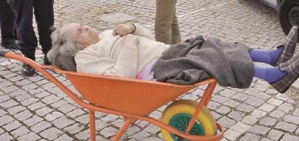 A idosa sendo transportada no carrinho de mão