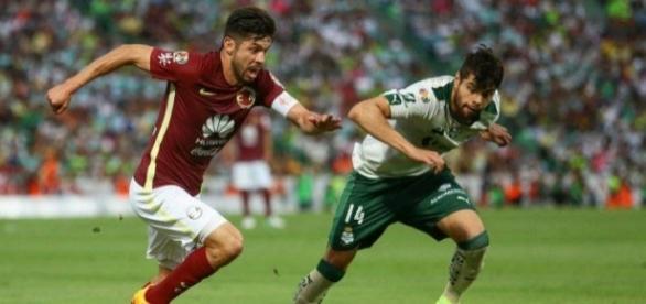 Oribe Peralta (izq.) enfrenta a Néstor Araujo durante la derrota del América. (via twitter - Replay Mx)