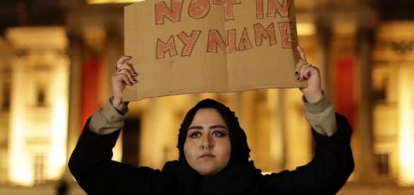 A Muslim woman holds a sign ... - go.com
