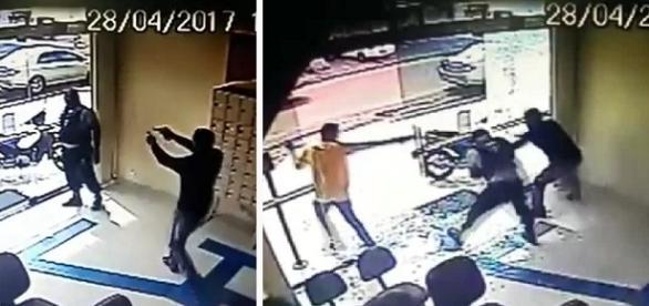Na imagem o momento em que um dos criminosos ameaça do vigilante da agência que ficou destruída. (Reprodução/Youtube/Arquivo Pessoal).