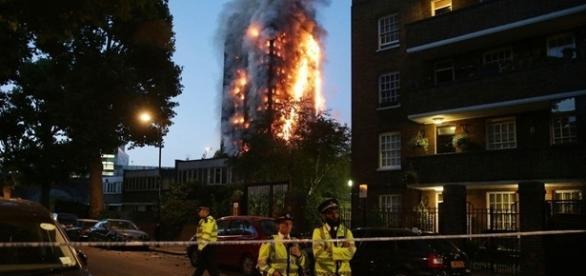 Policiais isolam área próxima ao prédio em chamas durante o amanhecer em Londres
