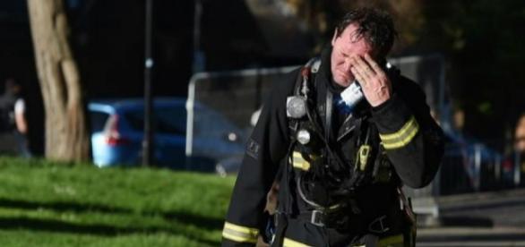 Um bombeiro em lágrimas na saída da torre