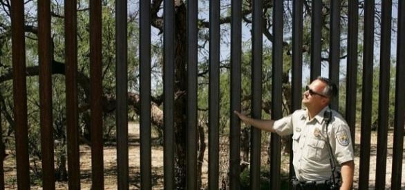 Patroler in uniform near border fence (wikimediacommons)
