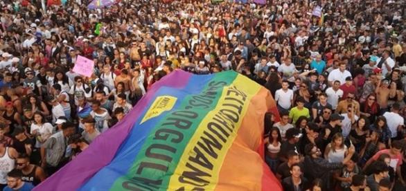 Bandeira da Anistia Internacional orgulhosamente nos braços dos que lutam pelo direito de amar
