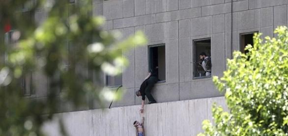 Homem entrega criança a guarda por uma janela do Parlamento iraniano após ataque