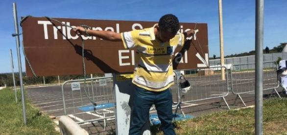 Homem se amarra à placa do TSE como forma de protesto