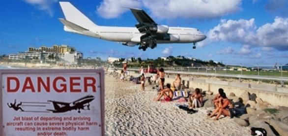 Turistas costumam se segurar na cerca do aeroporto Princess Juliana para ser atingidos de propósito pelo forte vento proveniente das aeronaves