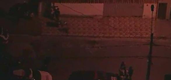 Policiais na frente da casa onde a mulher foi assassinada com golpes de espada (Foto: Captura de vídeo)