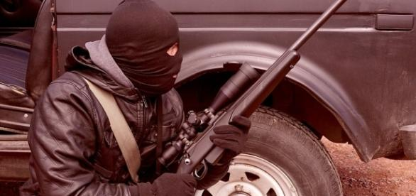 Faceof a modern terrorist replete with rifle.https://pixabay.com/en/criminal-terrorist-rifle-weapons-1563428/