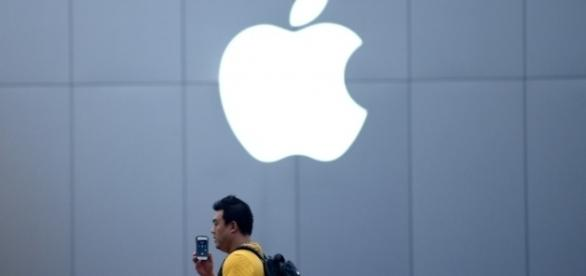 A Chinese man talks on his IPhone in front of an Apple store