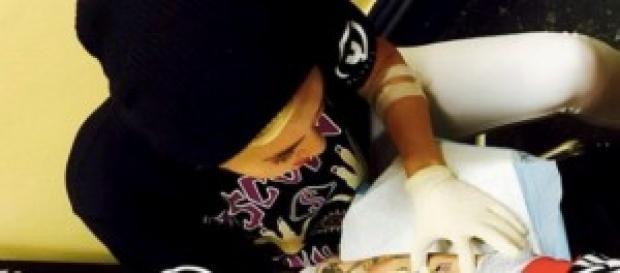 Miley Cyrus realizando uno de sus tatuajes.