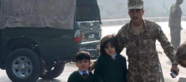 Un miembro del ejército ayuda a dos de los niños.