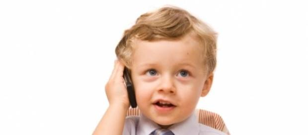 copil cu telefon mobil la ureche