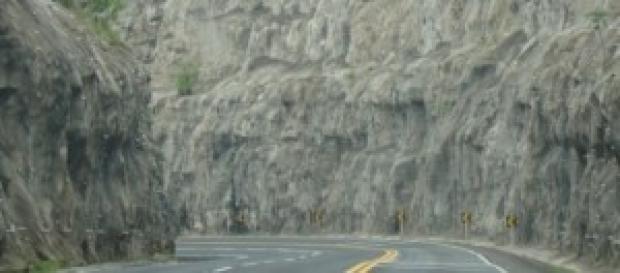Estrada longa, curvas e rochas.
