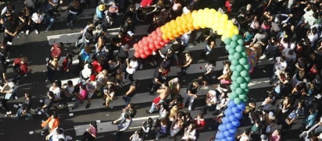 Várias pessoas se encontram na Parada Gay para assistir o desfile.